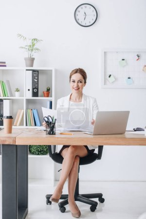 smiling business woman working with documents and laptop at workplace in modern office
