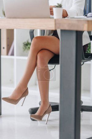 low section view of business woman working at table in office