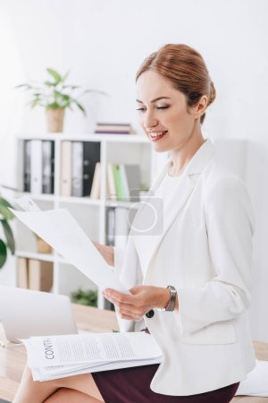 attractive business woman doing paperwork sitting on table in office