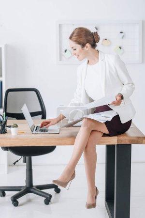Photo pour Femme d'affaires travaillant avec des documents et ordinateur portable tout en étant assis sur la table dans le bureau moderne - image libre de droit
