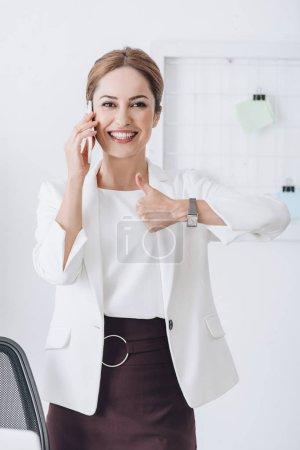 Foto de Alegre mujer de negocios hablando en smartphone y mostrando el pulgar hacia arriba en la oficina - Imagen libre de derechos
