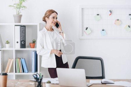 Photo pour Belle femme d'affaires professionnelle parlant sur smartphone au travail avec ordinateur portable - image libre de droit