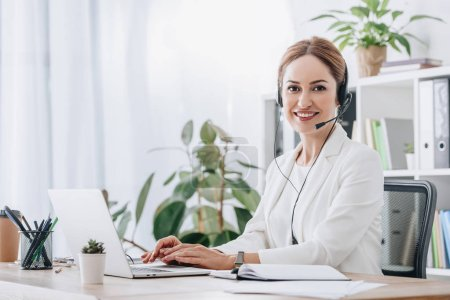 support operator working with headset and laptop in call center