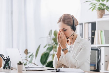 scared female operator working with headset and laptop in call center