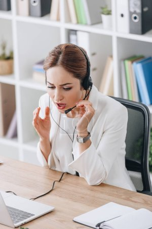 worried operator working with headset and laptop in modern office