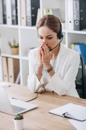 stressed support operator working with headset and laptop in call center