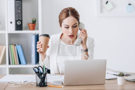 beautiful shocked businesswoman holding coffee to go while talking on phone and working with documents and laptop at workplace