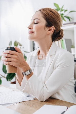 attractive businesswoman rest with closed eyes and holding coffee to go in office on coffee break