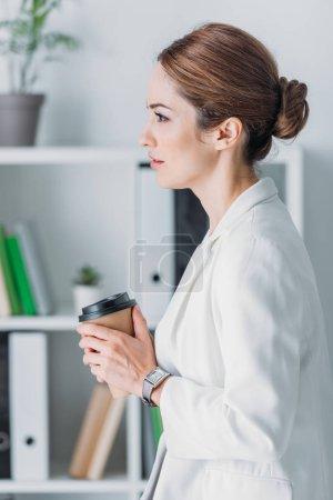 Photo pour Femme d'affaires exécutive avec tasse jetable de café dans le bureau moderne - image libre de droit