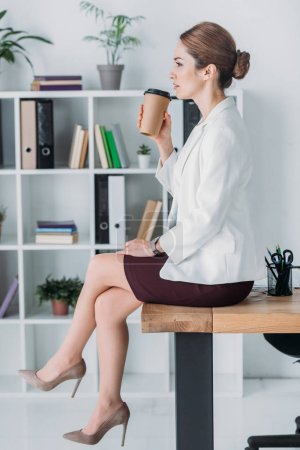 Photo for Businesswoman with paper cup sitting on table during coffee break in office - Royalty Free Image