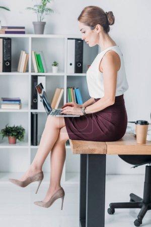 Photo pour Attrayant femme d'affaires travaillant avec ordinateur portable tout en étant assis sur la table dans le bureau - image libre de droit