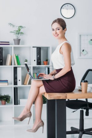 Photo for Smiling manager working with laptop while sitting on table in office - Royalty Free Image