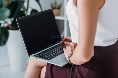 Photo pour Vue recadrée de femme d'affaires à l'aide d'un ordinateur portable avec écran blanc - image libre de droit