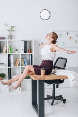 happy businesswoman with outstretched hands sitting on table during coffee break in modern office