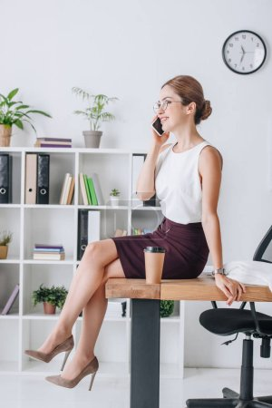 attractive businesswoman talking on smartphone while sitting on table in modern office
