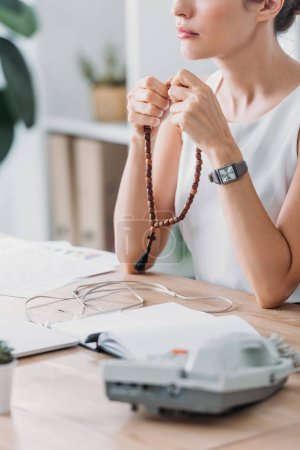 Photo for Cropped view of businesswoman praying with rosary beads in modern office - Royalty Free Image