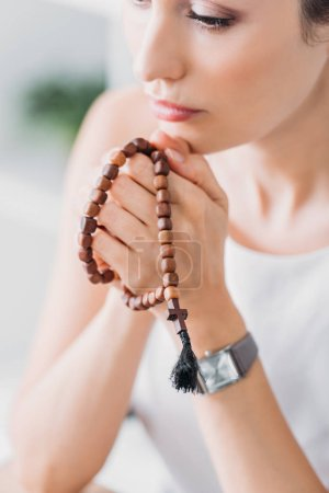 beautiful female prayer holding wooden rosary beads