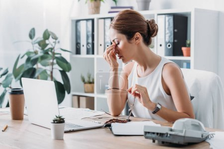 Photo pour Femme d'affaires fatigué, assis au milieu de travail avec ordinateur portable au bureau moderne - image libre de droit