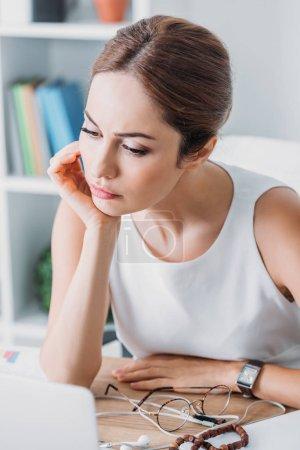 Photo pour Séduisante femme d'affaires pensif assis au milieu de travail dans le bureau moderne - image libre de droit