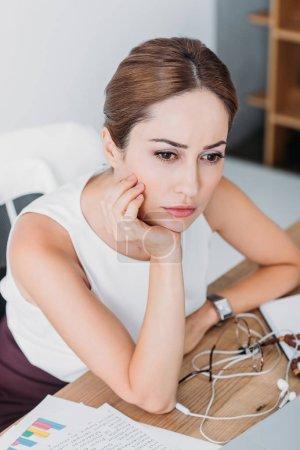 Photo pour Belle femme d'affaires pensif, assis au milieu de travail dans le bureau moderne - image libre de droit