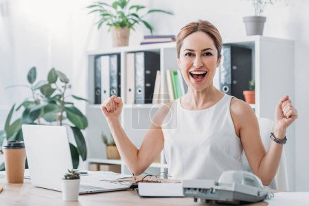 Photo for Beautiful excited businesswoman celebrating success at workplace with laptop - Royalty Free Image