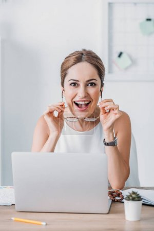beautiful surprised businesswoman sitting at workplace and looking at camera