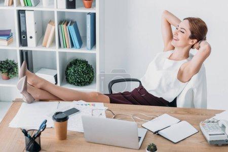 Photo pour Adulte femme heureuse assis dans la chaise main derrière la tête au milieu de travail - image libre de droit