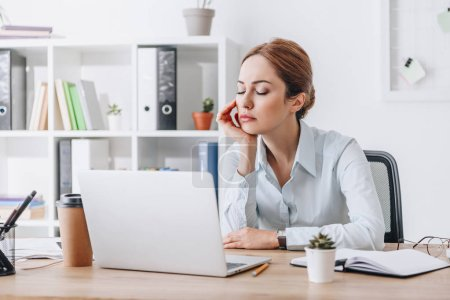 Photo for Exhausted adult businesswoman sleeping at workplace in modern office while leaning on hand - Royalty Free Image