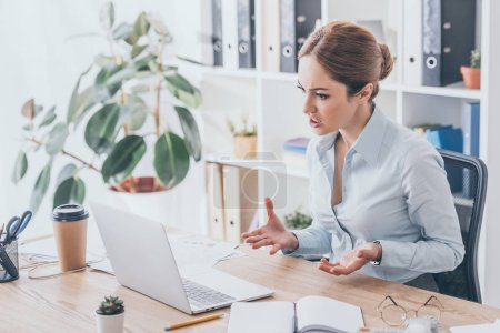 stressed adult businesswoman looking at laptop screen at office