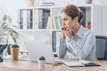 thoughtful adult businesswoman sitting at workplace and looking away
