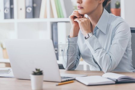 Photo for Cropped shot of thoughtful adult businesswoman sitting at workplace - Royalty Free Image