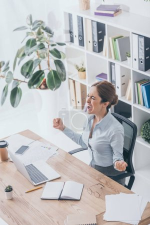 high angle view of stressed adult businesswoman screaming at workplace