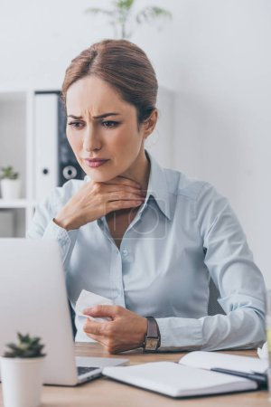 suffering sick businesswoman with sore throat trying to work at office