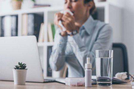Photo pour Debout sur la table de travail avec floue businesswoman éternuement assis sur fond de médicaments - image libre de droit
