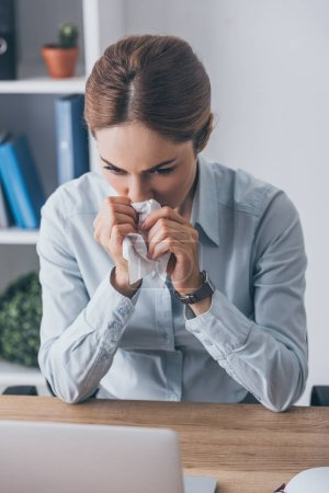 sick adult businesswoman with runny nose holding paper napkin and sitting at workplace