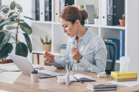 sick adult businesswoman sitting at workplace with plastic jar of pills and water