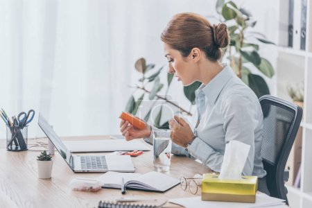 side view of sick adult businesswoman sitting at workplace with plastic jar of pills and water