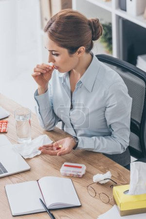 high angle view of sick adult businesswoman taking pills at workplace