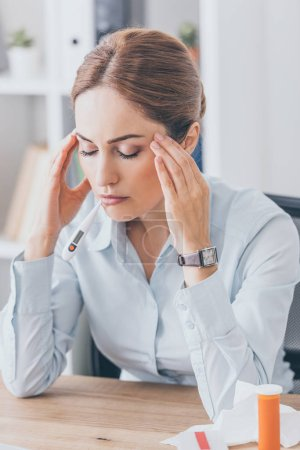 adult sick businesswoman with headache sitting at workplace with closed eyes