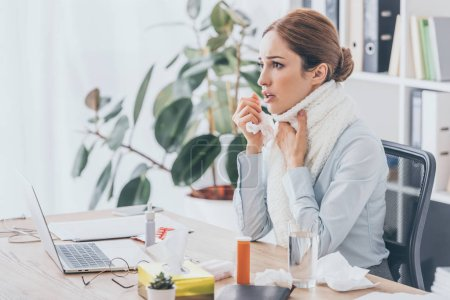 adult sick businesswoman with flu sitting at workplace in scarf