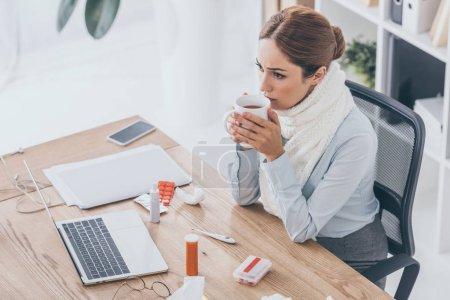 Photo pour Vue d'angle élevé de femme malade en écharpe, assis au milieu de travail et boire du thé - image libre de droit
