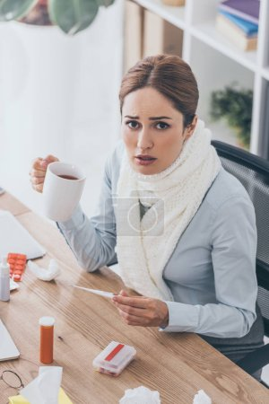 high angle view of sick businesswoman in scarf holding cup of tea and electric thermometer sitting at office and looking at camera
