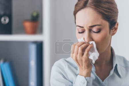 close-up portrait of businesswoman with runny nose at office