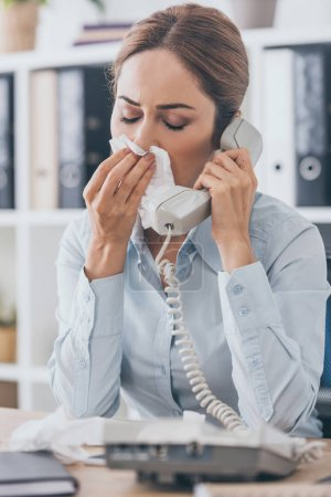 close-up portrait of diseased businesswoman with runny nose talking by wired phone at office