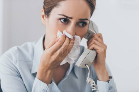 close-up portrait of sick businesswoman with runny nose talking by wired phone