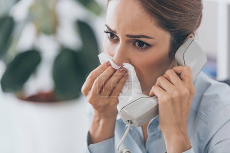 close-up portrait of businesswoman with runny nose talking by wired phone