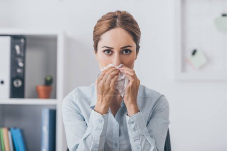 sick businesswoman with paper napkin having runny nose and looking at camera at office