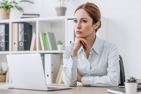thoughtful adult businesswoman sitting at workplace at office and looking away