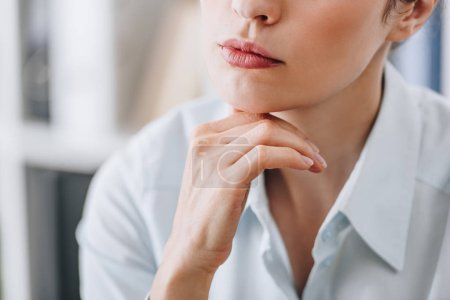 cropped shot of businesswoman touching chin with hand at office