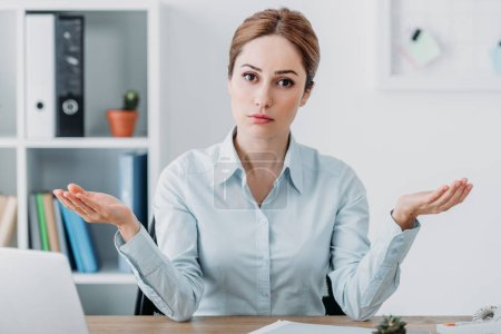 serious adult businesswoman looking at camera and gesturing with hands at office